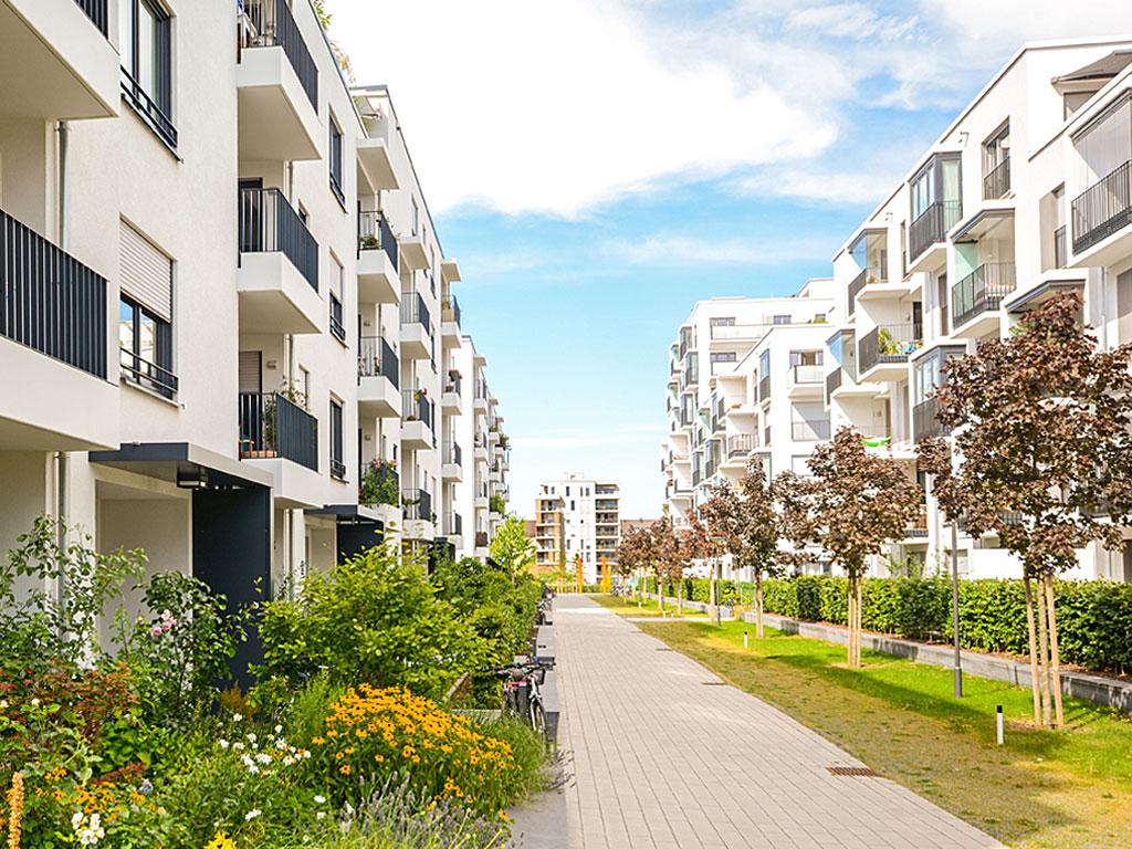 Das Foto zeigt Mehrfamilienhäuser in einem Wohngebiet (© by ah_fotobox - Andreas*H / Moment Open / Getty Images / 574843943 / Bildausschnitt, eigene Bearbeitung)
