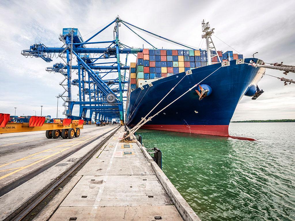 Das Foto zeigt ein Frachtschiff in einem Hafen (© Thierry Dosogne / DigitalVision / Getty Images / 852075234 / Bildausschnitt)