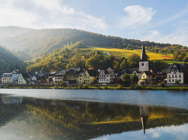 Das Foto zeigt eine Ortschaft an einem Fluss (© Marco Bottigelli / Moment / Getty Images / 932658198 / Bildausschnitt, eigene Bearbeitung)